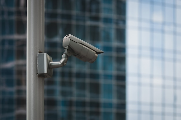 Zewnętrzna kamera bezpieczeństwa na słupie przed szklaną ścianą budynku