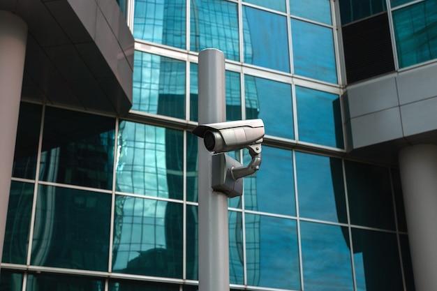 Zewnętrzna kamera monitorująca przy szklanej fasadzie budynku