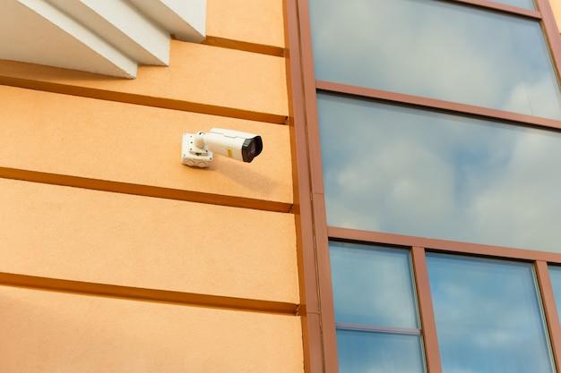 Zewnętrzna kamera nadzoru na elewacji budynku. pojęcie bezpieczeństwa, ochrony oraz prawa i porządku.