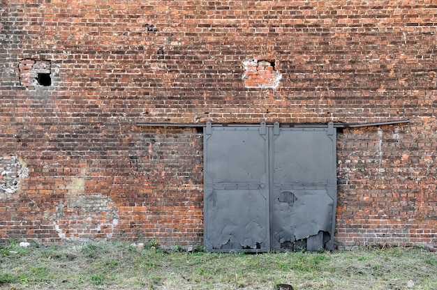 Zewnętrzna ściana z czerwonej cegły starej fabryki z żelaznymi bramami stary budynek tekstura tło