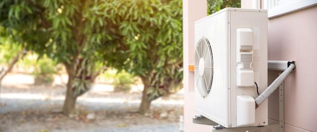 Zewnętrzna sprężarka klimatyzatora z dzieloną ścianą zamontowana na zewnątrz budynku.