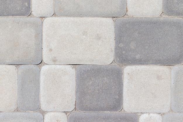 Zewnętrzna tekstura płytek betonowych w różnych odcieniach szarości