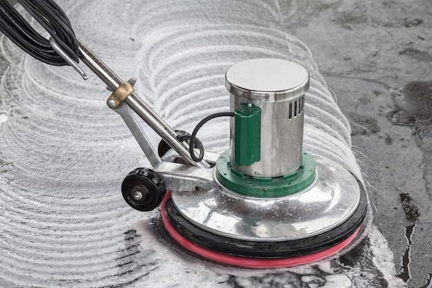 Zewnętrzne czyszczenie podłóg z kamienia czarnego przy użyciu maszyny do polerowania i środków chemicznych