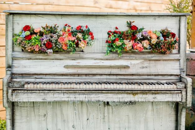 Zewnętrzne dekoracyjne retro białe pianino z kwiatowymi ornamentami i kaskadą wodną