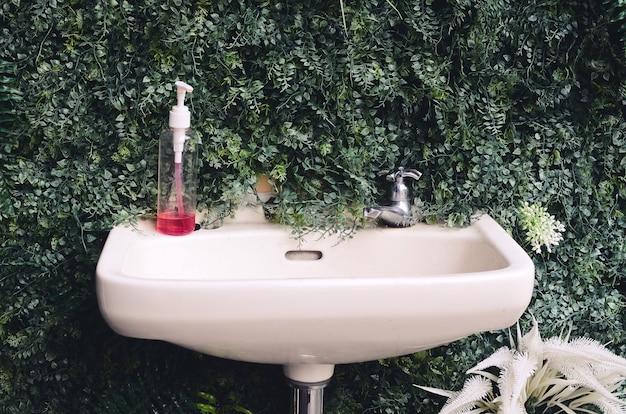 Zewnętrzne miejsce do mycia rąk na tle sztucznych roślin