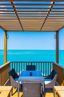 Zewnętrzne patio z pustym krzesłem i stołem z widokiem na ocean morski z widokiem na białe chmury i błękitne niebo