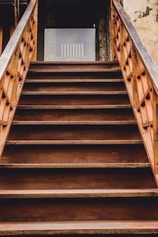 Zewnętrzne stare drewniane schody z balustradą. poręcze, tralki