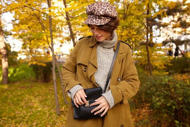 Zewnętrzne zdjęcie modnej młodej brunetki z fryzurą bob stojącej nad miejskim ogrodem w ciepły jesienny dzień, szukając czegoś w swojej czarnej skórzanej torbie