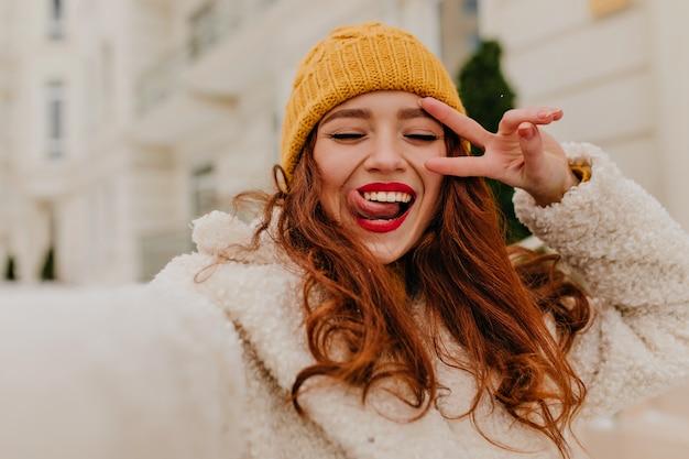 Zewnętrzne zdjęcie uśmiechniętej niesamowitej dziewczyny cieszącej się zimą. atrakcyjna imbirowa modelka dokonywanie selfie.