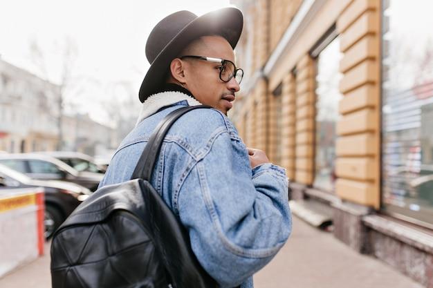 Zewnętrzne zdjęcie z tyłu pewnego siebie afrykańczyka w dżinsowej kurtce spacerującego po ulicy. stylowy czarny facet patrząc na wizytówkę.