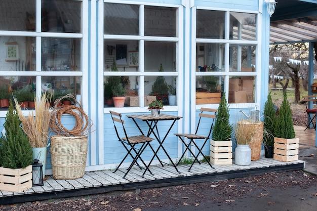 Zewnętrzny dom w kolorze niebieskim z pięknym tarasem ozdobnym zielenią roślin