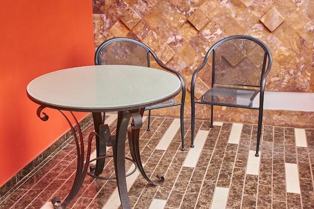 Zewnętrzny taras z małym okrągłym stołem i dwoma metalowymi krzesłami na popołudnie