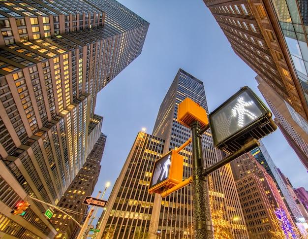 Zewnętrzny widok nowoczesnych wieżowców midtown z ulicy w nocy - nowy jork.