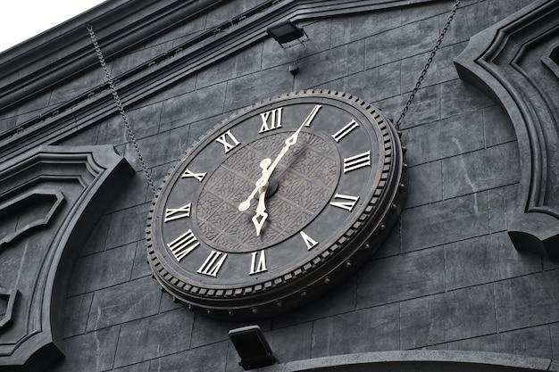 Zewnętrzny zegar z rzymskimi cyframi na elewacji budynku. antyk vintage zegar w stacji kolejowej.