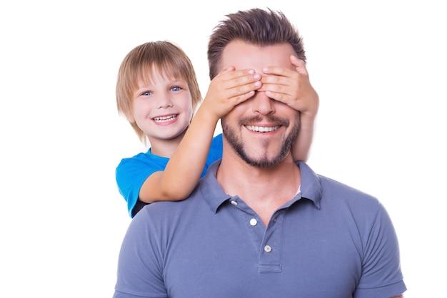 Zgadnij kto! zabawny mały chłopiec zakrywający oczy ojca rękami i uśmiechający się, gdy obaj stoją na białym tle na białym tle