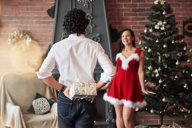 Zgadnij w której ręce, w obu. człowiek stoi i trzyma pudełko za. kobieta w czerwonej sukience otrzyma teraz prezent świąteczny od chłopaka.