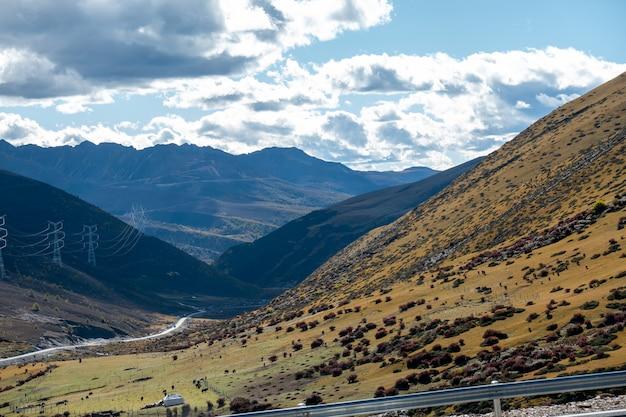Zginaj na wiejskiej drodze prowadzącej do parku narodowego yading, daocheng, prowincja syczuan, chiny.
