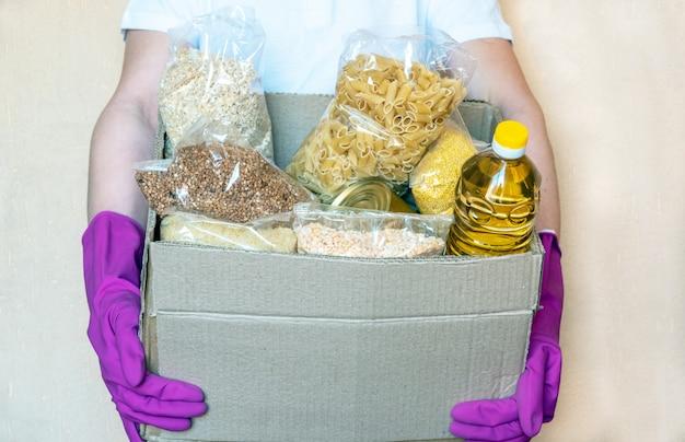 Zgłaszaj się w rękawiczkach ochronnych, wkładając jedzenie do pudełka od darowizn. pracownik dostawy człowiek w czerwonej kamizelce opakowanie z jedzeniem. usługa kwarantanny pandemiczny koronawirus.