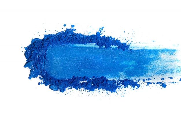 Zgnieciony cień do oczu niebieski na białym tle.