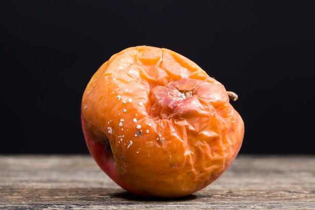 Zgniłe jabłko pokryte pleśnią, zepsute jedzenie, grzyb i pleśń zniszczyły dojrzałe jabłko podczas naruszenia warunków przechowywania