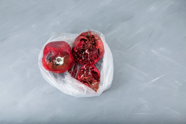 Zgniłe zepsute owoce granatu w plastikowej torbie