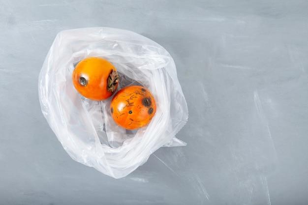 Zgniłe zepsute persimmon w plastikowej torbie niewłaściwe przechowywanie żywności redukcja odpadów organicznych