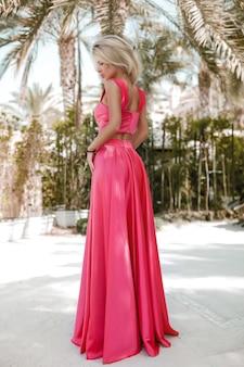 Zgrabna blondynka nad morzem w dubaju, palmy, gorące, przepiękne sukienki, strzelanie z letniego słonecznego stylu życia, machanie w sukience od wiatru, spokój i relaks przy basenie, fryzura, makijaż