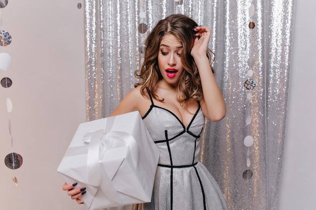 Zgrabna ciemnowłosa kobieta w sukience wyrażająca zaskoczone emocje na przyjęciu urodzinowym. zdziwiona romantyczna dziewczyna patrząc na duże pudełko na prezent.
