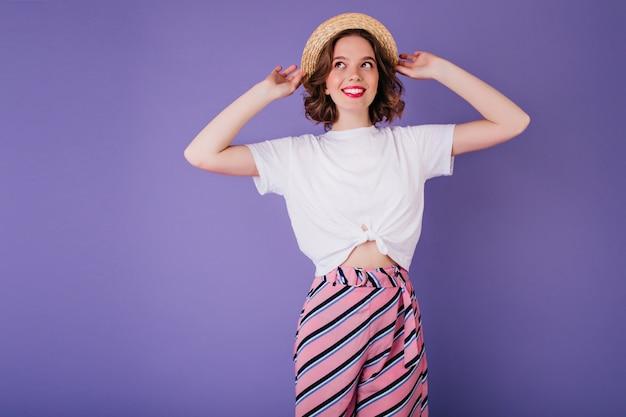 Zgrabna dama w białej koszulce i kapeluszu vintage pozuje z uśmiechem. kryty zdjęcie zadowolony europejskiej dziewczyny w pasiaste spodnie na białym tle na jasnej fioletowej ścianie.