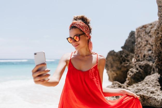 Zgrabna dziewczyna w błyszczących okularach przeciwsłonecznych, dzięki czemu selfie w weekend w letnisku. odkryty strzał błogiej opalonej kobiety, która robi sobie zdjęcie podczas chłodzenia na plaży oceanu.