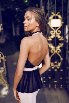 Zgrabna dziewczyna w czarno-białej sukience, stojąca przy bramie, machająca włosami, wesoła, moda, styl, modelka, impreza, impreza, plecy, białe buty, szpilki, zabawa, makijaż