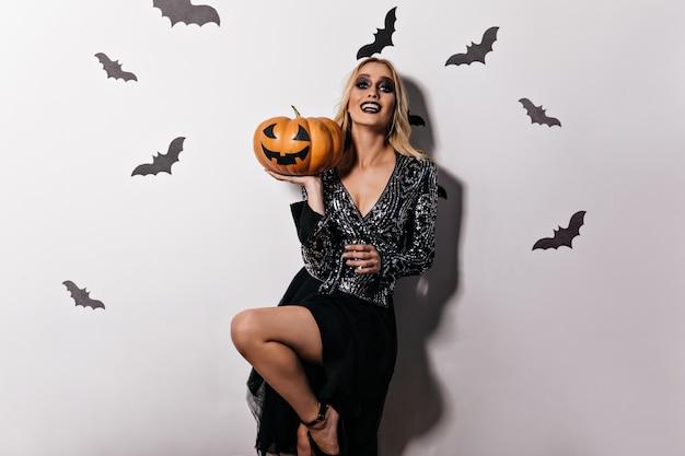 Zgrabna dziewczyna w eleganckiej sukni trzyma dyni halloween. oszałamiająca blond wiedźma bawi się w karnawale