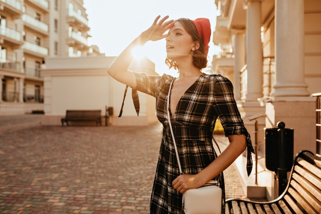 Zgrabna dziewczyna w eleganckiej szarej sukience patrząc na odległość. plenerowy portret uroczej krótkowłosej pani w czerwonym berecie.