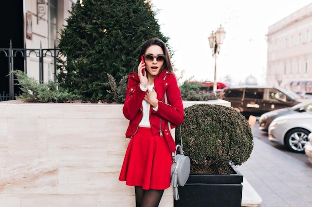 Zgrabna dziewczyna w modnej czerwonej spódnicy rozmawia przez telefon w pobliżu zielonego krzewu