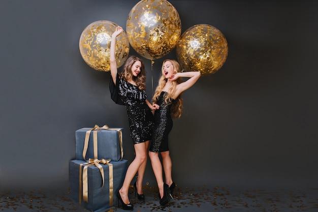 Zgrabna dziewczyna z długimi kręconymi włosami bawiąca się z siostrą podczas urodzinowej sesji zdjęciowej. urzekające panie w modnych sukienkach czekające na przyjęcie, stojące przy prezentach.