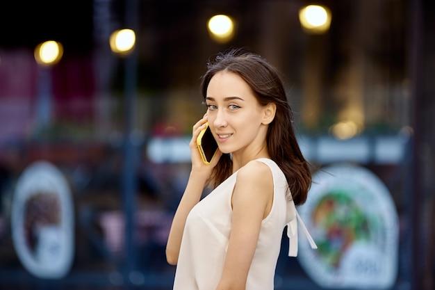 Zgrabna dziewczyna z telefonem komórkowym chodzi na zewnątrz w ciągu dnia