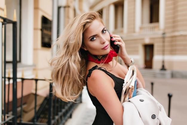 Zgrabna europejska dziewczyna o niebieskich oczach pozuje z telefonem podczas spaceru po mieście