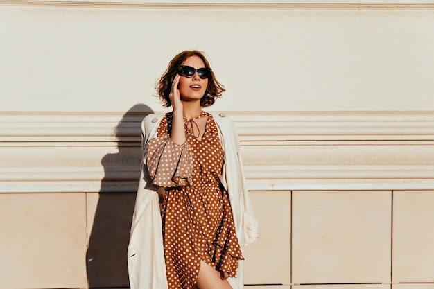 Zgrabna kobieta dotyka jej okularów w sukience vintage. odkryty strzał zainteresowanej zrelaksowanej dziewczyny w brązowym stroju.