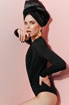 Zgrabna kobieta gryzie palec na różowej ścianie
