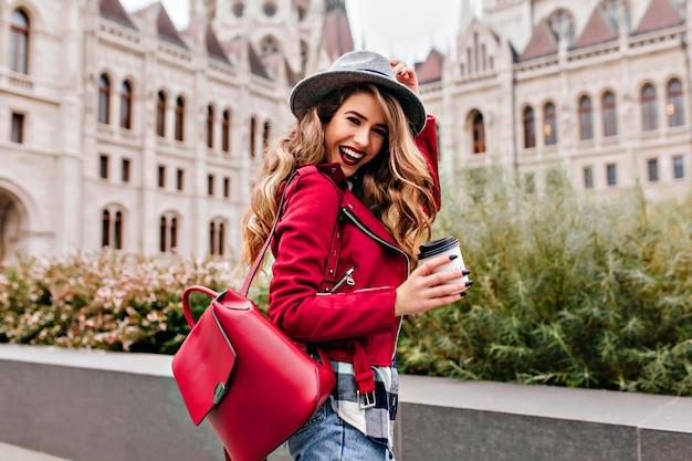 Zgrabna kobieta z falującymi włosami śmiejąca się podczas zwiedzania starej części miasta