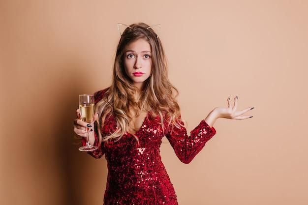 Zgrabna kobieta z lśniącymi kręconymi włosami stojąca przy lampce szampana na białym tle na lekkiej ścianie