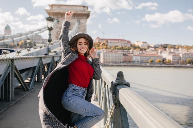 Zgrabna marzycielska kobieta śmieszne pozowanie na moście na tle rzeki