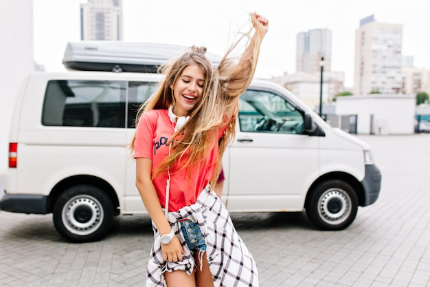 Zgrabna młoda kobieta z długimi włosami taniec relaksujący na świeżym powietrzu z uśmiechem i zamkniętymi oczami
