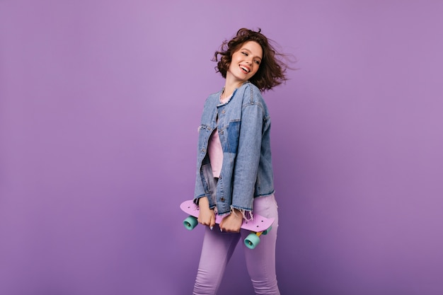 Zgrabna przystojny dziewczyna pozuje z radosnym uśmiechem. piękna brunetka dama z longboard chłodzenie kryty.