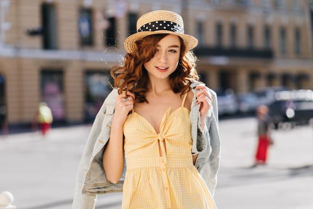 Zgrabna ruda dziewczyna w letnim kapeluszu pozuje na ulicy. urocza kręcona kobieta w żółtej sukience stojąca przed budynkiem.
