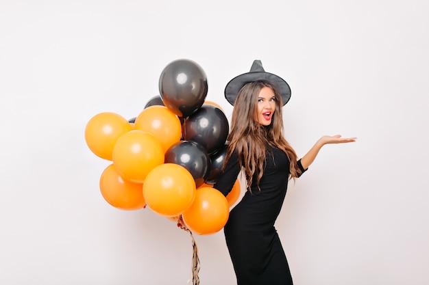 Zgrabna śmieszna kobieta pozuje w stroju karnawałowym czarownicy