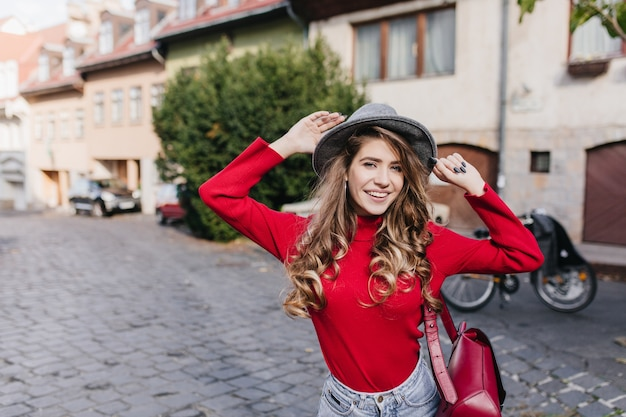 Zgrabna wspaniała kobieta w sweterku tańczy obok domu z błogim uśmiechem