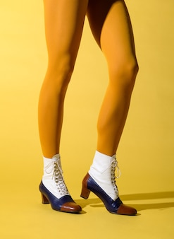 Zgrabne nogi kobiety w musztardowym kolorze collant i wysokich butach tritone w stylu retro