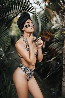 Zgrabnie opalona kobieta w stroju kąpielowym, dotykając szyi na tle przyrody. odkryty strzał ładnej kobiety w turbanie za pomocą opasek na oczy.