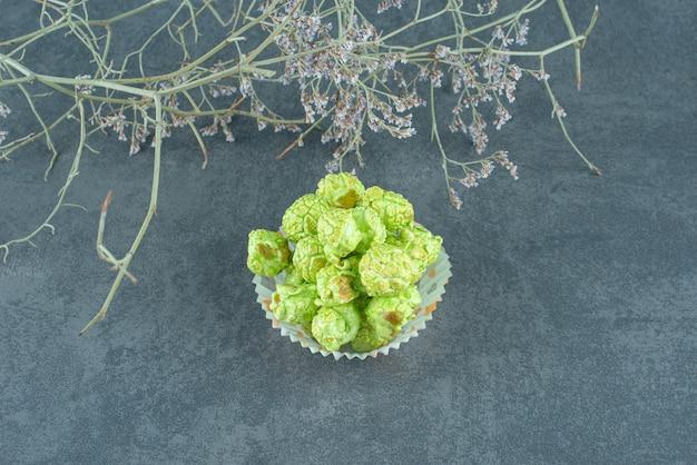 Zgrabny stos zielonych cukierków popcorn obok ozdobnych gałęzi na marmurowym tle. zdjęcie wysokiej jakości